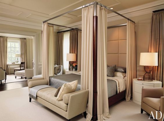 A traditional bedroom by Powell & Bonnell features a four-poster with neutral bed curtains.