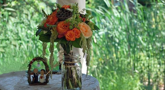 Cascading Boho style bouquet with peach, coral, brown and green flowers.