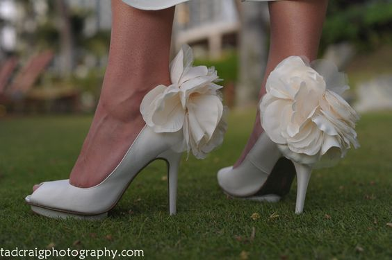 White wedding shoes with large flower on the back. Picture taken by Tad Craig Photography