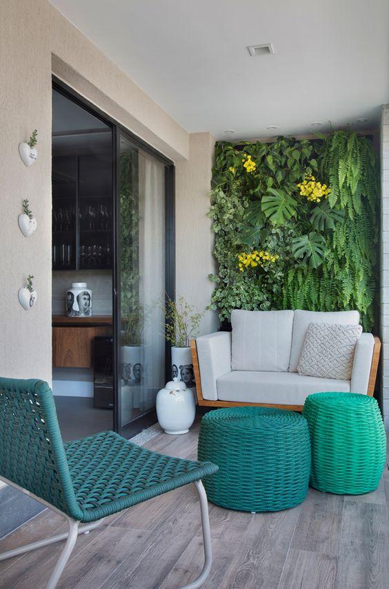 Apartamento tem jardim vertical na varanda e decoração neutra