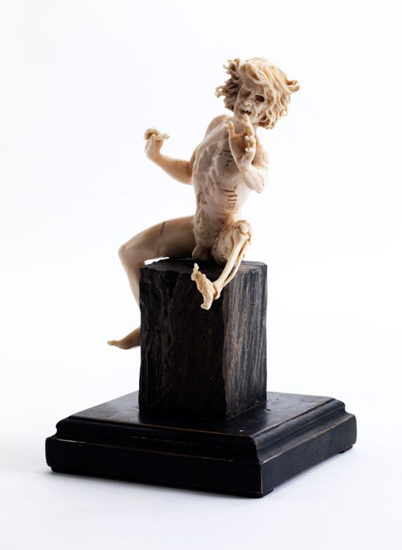 """Vanitasfigur in Elfenbein. Höhe der Figur: 15 cm. In Gestalt eines auf einem Holzblock sitzenden Mannes, dessen linke Hälfte modrig verwest, die rechte noch lebensnah erhalten ist. Sitzhaltung in aufschreckender Weise nach vorne gerichtet, der linke Fuß bereits zum Skelett verwest, am Schenkel aus Löchern hervortretende Würmer. Die Figur in Art des """"Furienmeisters"""". -HAMPEL Fine Art Auctions Munich-"""