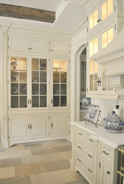 Elegant French inspired white kitchen with stone floors, white glass fronted cabinetry, and blue and white porcelain accessories in chateau (The Enchanted Home). #frenchcountry #whitekitchen #traditional #timeless