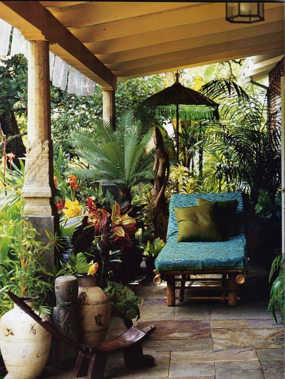 bursting with tropical plants, art, sculpture, umbrellas, and furniture hidden…