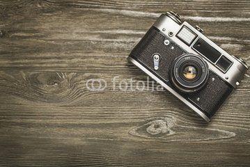 Camera. vintage old camera on brown wooden background. room for