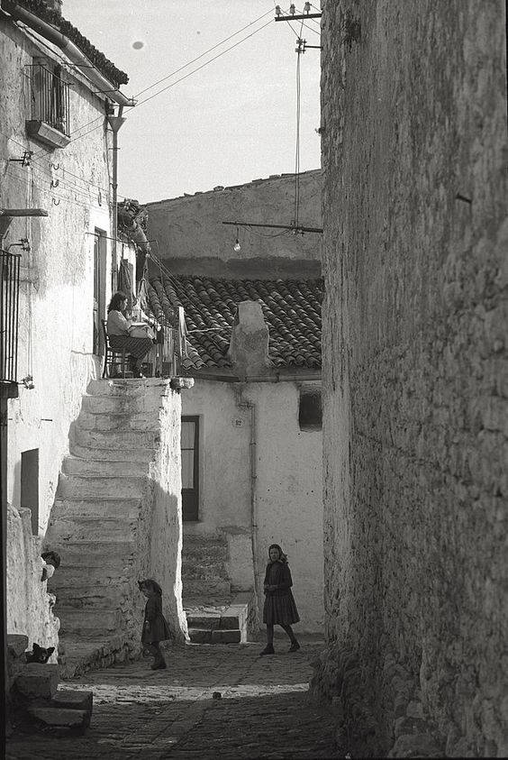 A view of San Giovanni Rotondo (Fg); a woman embroidering seated at the top of the steps of her house, children play in the street. Italy. (Photo by Mario De Biasi/Mondadori Portfolio via Getty Images)