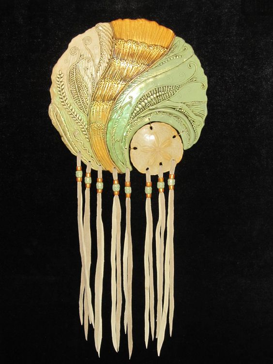 Polymer clay wall hanging with fossil and leather by Karen Brueggemann