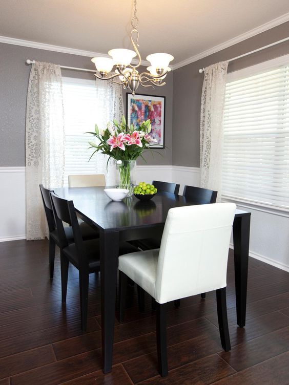 Chair rail molding divides two-toned walls in this neutral dining room. Sheer curtains and white blinds feel crisp and airy against the dark hardwood floor and black dining table. Fresh flowers and a bowl of fruit add a refreshing splash of color.