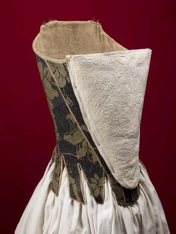 Korset of rijglijf van wollen damast, blauw met groene bloemen, met rijgsluiting middenvoor en een schootje van losse pandjes | Modemuze