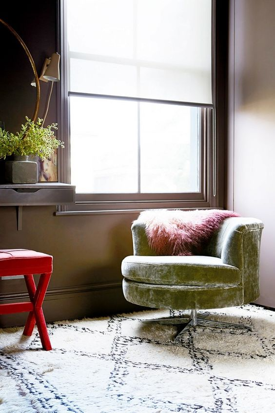 Bedroom corner with chocolate brown walls, and a green velvet armchair