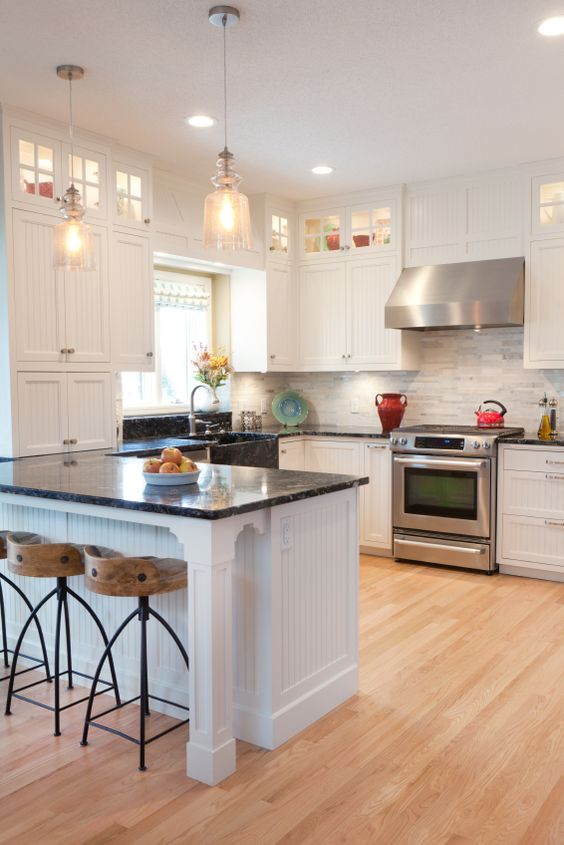 The crisp textures on the white cabinetry of this kitchen add an element of detail that pairs favorably with the intricate tile backsplash. Light, warm toned hardwood flooring ups the brightness factor.