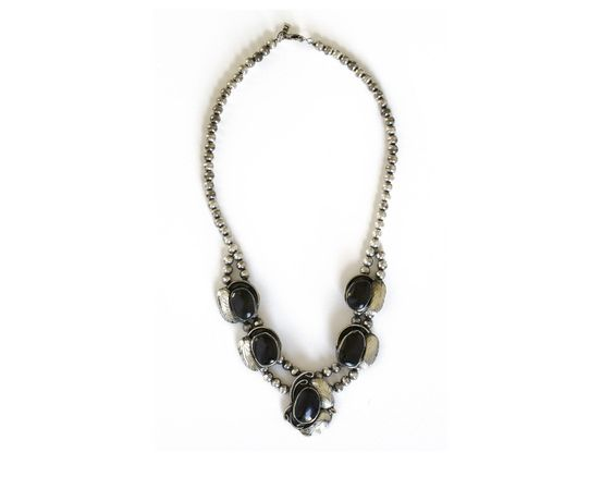 """A statement necklace with engraved detailing in antique silver. Approx. 20"""" in length. Note: This necklace is made with a natural stone or shell. Shading, size, and color may vary."""