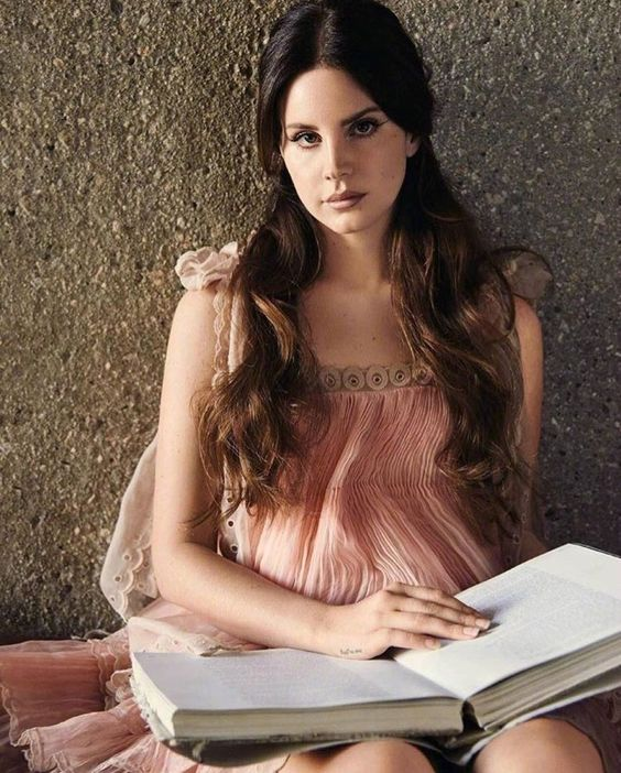 Lana Del Rey photoshoot in pink babydoll dress while holding a book open 2017