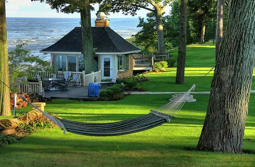 This is damn near close to perfection. A pretty little cottage overlooking the ocean, surrounded by emerald green grass. The hammock is just icing.