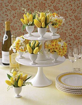 Stacking two cake stands make a wonderful Easter centerpiece.  I'd mix in yellow dyed eggs among these flowers.