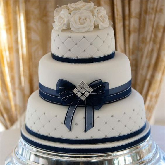 Gorgeous cake combining royal blue and silver colour theme with roses for bouquet.