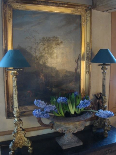 This is a good example of advice I give about framing- use a gold (or silvery-gold) frame. You don't have to worry about wood tones & it draws your eye. The subtle blues in the art are enhanced by the blue shades & the flowers. They frame the picture nicely too.