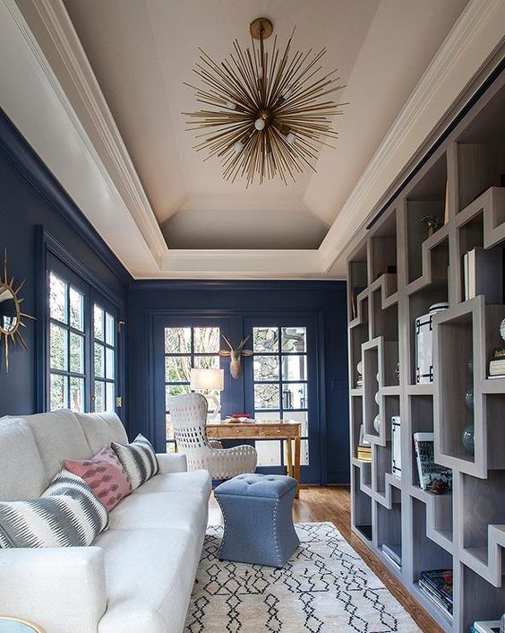 Long blue contemporary living room features an Arteriors Zanadoo Chandelier hung from a tray ceiling lighting blue walls framing French patio doors.