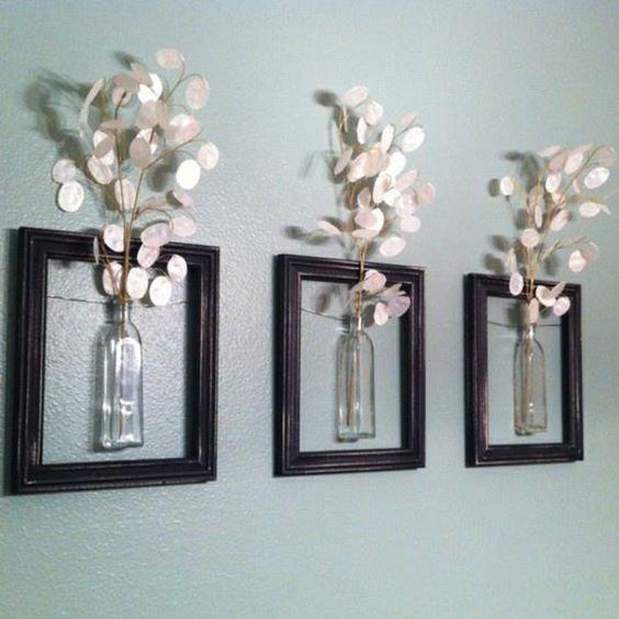 wanddekoration aus weißen blumen in kleinen gläsernen vasen - drei