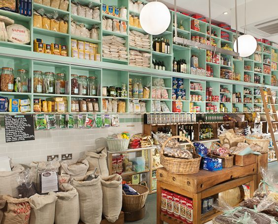 The pale green colour of the shelving in this store make the overly-cluttered grocery store appear lighter, fresher and larger making the clutter appear organized.: