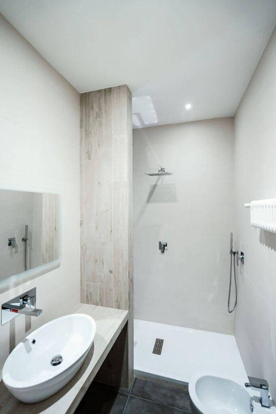 Im Bad selbst sehen wir die leichte natürliche Holz Akzente schmücken den minimalistischen Raum. Features wie das weiße Schiff Waschbecken und Wand montierte Wasserhahn erhöhen den Wow-Faktor.