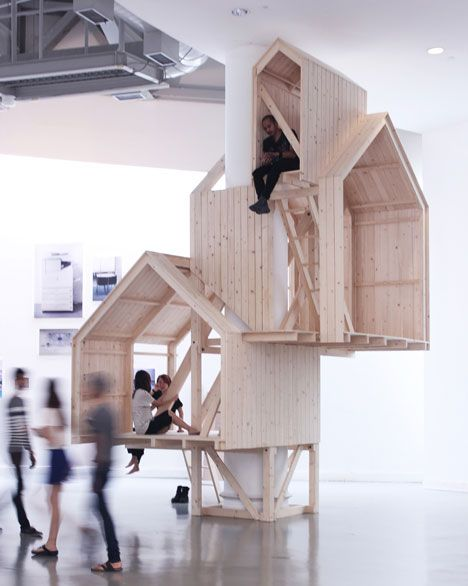 """Shelter of Nostalgia by Thai designer Worapong Manupipatpong    """"I want to bring back the memory of when we experienced space with our small bodies, but with large imagination and borderless freedom,"""" he explains.    These tree house-like cabins are built up around the column of a building rather than over the branches of a tree.    The three wooden playhouses overlap one another as they stack up around the column and ladders connect each floor to the one above."""