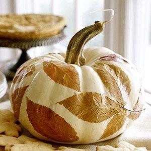 Mod Podge flattened leaves onto a white pumpkin.