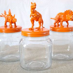 Glass storage jars with orange dinosaurs on the lids.