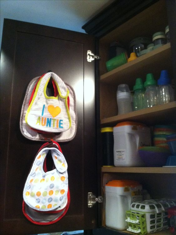3M hooks inside cabinet door to hang baby bibs. Baby organization.