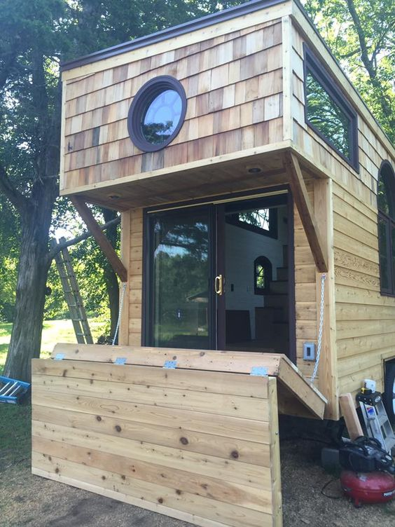 Old World Vermont tiny house Drop down patio that also protects