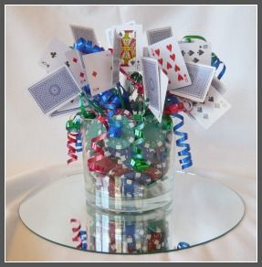 A fundraising event casino night centerpiece... It's simple, but I like it. I'd use red or black print cards & ribbon for mine.