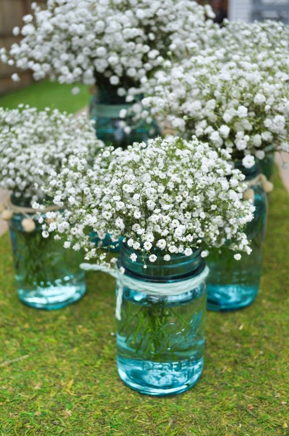 Babys breath... lots of baby's breath s probably cheap and looks cool in a big bunch with blue mason jars as center pieces