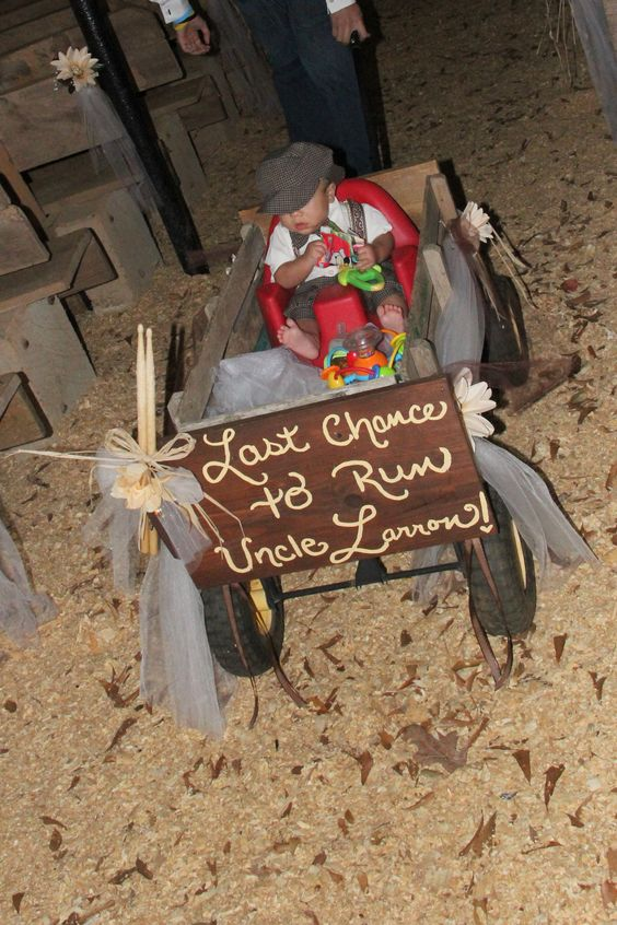 Ring bearer pulled in wagon at rustic wedding