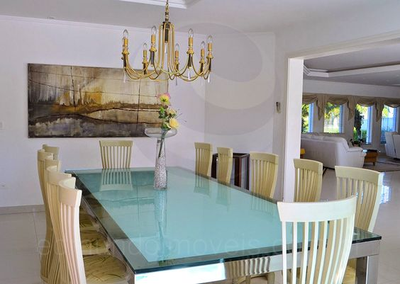 Em um ambiente separado, a sala de jantar possui um exuberante lustre pendente dourado, que deixa o ambiente muito bem iluminado e receptivo, e pode acomodar até 12 pessoas ao redor da mesa com tampo de vidro.