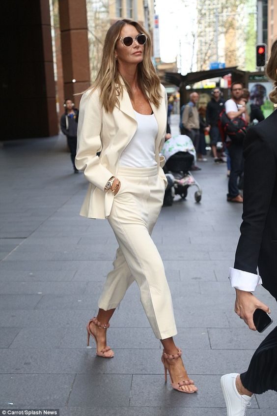 Sun kissed: The 52-year-old chose a cream and blush pink ensemble accessorised with hints of gold - highlighting her bronzed skin