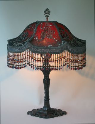 antique ornate metal table lamp bases hold Vader shades dyed wine red to midnight blue. Vintage black, silver and pewter colored laces and beaded nets cover the shades. Victorian era appliqués overlay the center panels. The hand beaded glass fringe contains all the colors that are in the shades.