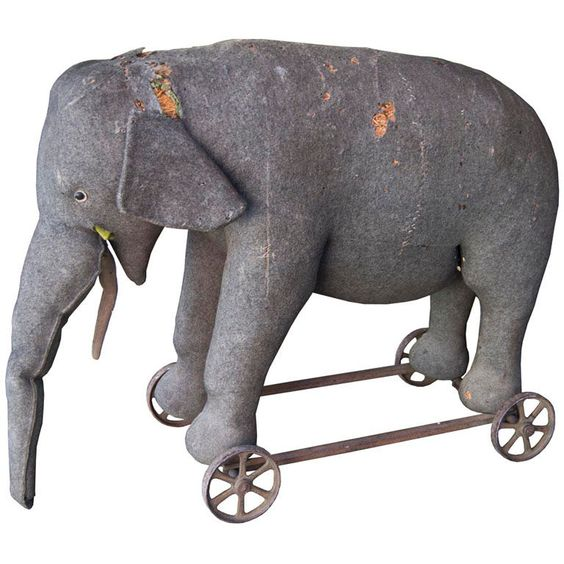 Steiff Riding Elephant  Germany  1910s  Rare Steiff riding elephant made of rush wrapped in dark grey felt with signature brass grommet on top right side of elephant on metal wheels, with natural wear and tear, missing right side ear and left side tusk and tail.