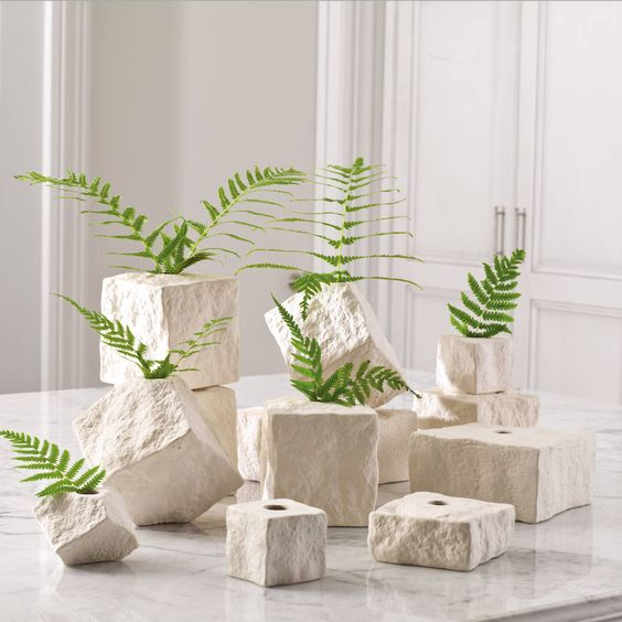 These water-tight vases are made of ceramic to resemble cut stone blocks. They can be stacked, clustered, massed out or used individually.  Use them for buds, twigs, or greenery; they also add texture and form as sculptural pieces | domino.com