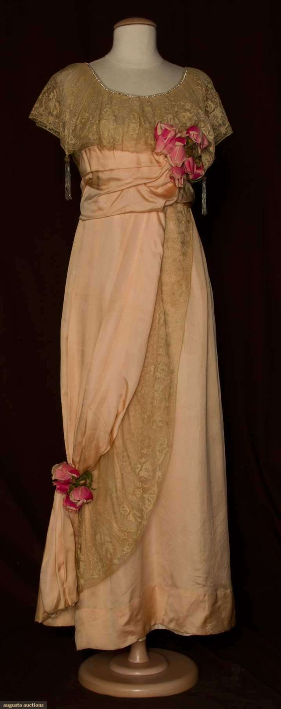 """Silk and lace evening gown, 1912; Light weight satin, empire waist, low round rhinestone edged neckline with deep lace flounce and four beaded tassels, skirt with side drape panel, cloth roses at bust and draped panel, B 34"""", Hi-W 27"""", L 54 """", label """"Thurn"""""""
