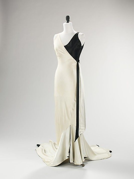 1930 Jessie Franklin Turner gown - the slipper satin and bias-cut construction used in this evening ensemble epitomizes the body-conscious drama of the 1930s. Turner's  expression of this drama is shown in the graphic combination of black and white and the inventive cut of the three pieces--the dress, the jacket, and the overbodice. (Dress)