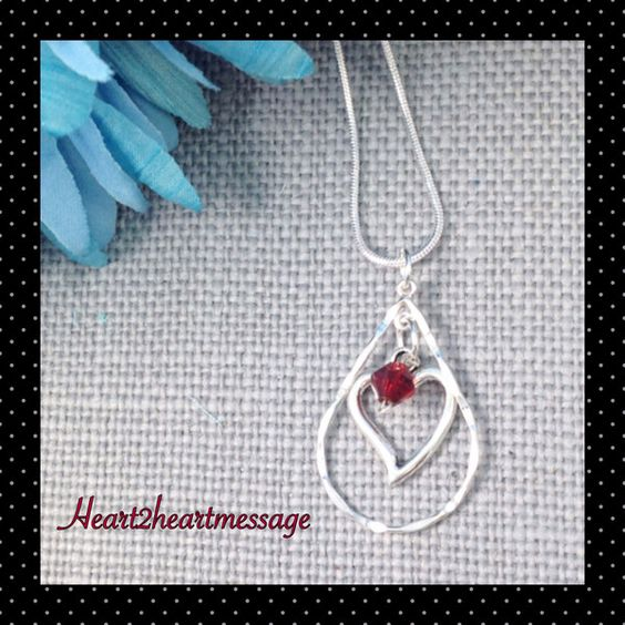 """Delicate Sterling Silver tear Drop necklace with a silver heart and a red Swarovski Bead dangling in the center. Pendant measures approximately 1 1/2"""" X 1"""" and"""