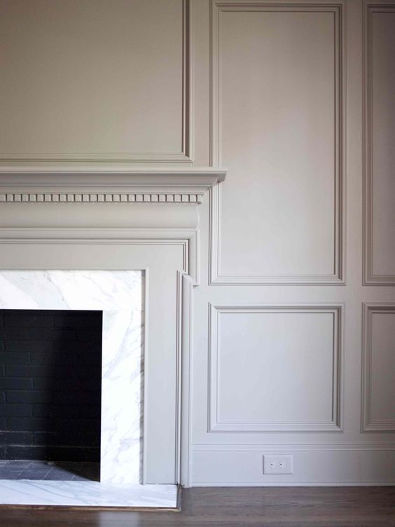 fireplace mantel surrounded by panel walls millwork