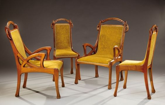 EUGENE GAILLARD (1862-1932) ensemble de salon comprenant deux fauteuils et deux chaises en noyer à dossier droit partiellement ajouré à motifs floraux sculptés.