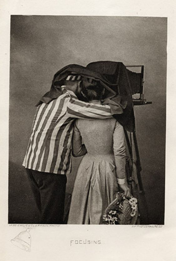 "This image called ""Focusing"" by Miss Emily V. Clarkson was printed by the NN Photogravure. company Since we are a couple absorbed in all things photographic we find this couple sharing a darkcloth especially poignant.:"