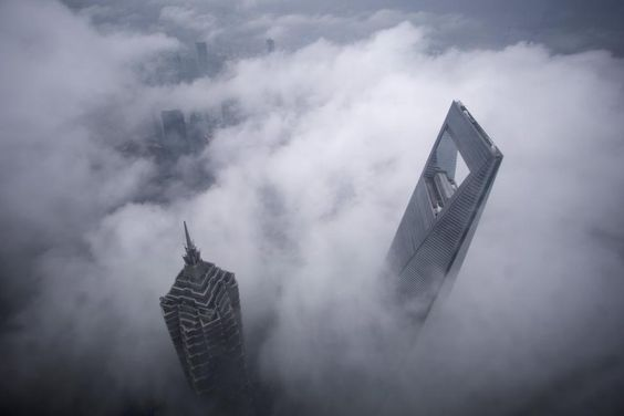 Skyscrapers Shanghai World Financial Center (R) and Jin Mao Tower are seen during heavy rain at the financial district of Pudong in Shanghai May 15, 2015. REUTERS/Aly Song