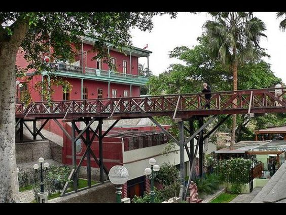Bridge in Barranco with a red house and palm tree in the back