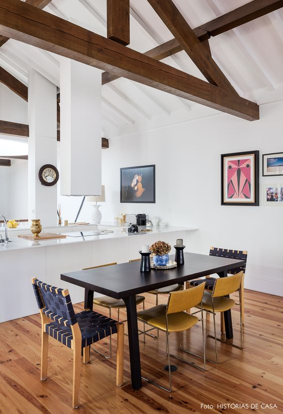 Sala de jantar integrada com cozinha tem mesa preta com cadeiras na mesma cor do designer Alvar Aalto.