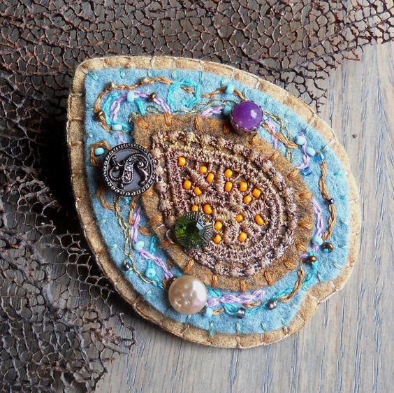 Wool felt brooch with hand dyed vintage applique, beads, vintage buttons, and embroidery. $50.00, via Etsy.
