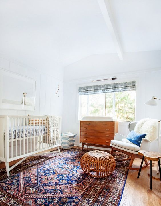 Bright and earthy nursery with rocking chair, midcentury dresser, and Persian rug.: