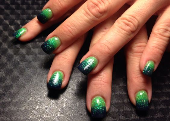 Seattle Seahawks ombré acrylic nails with football lace striping on accent nail.