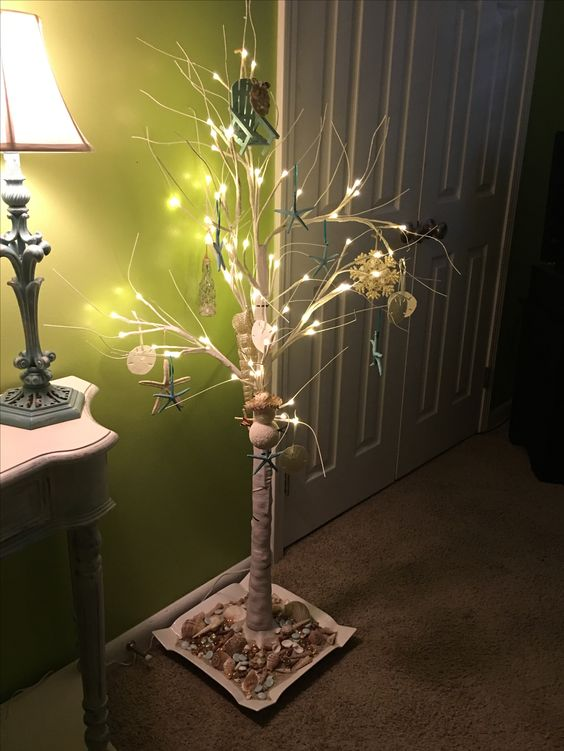 White birch tree with beach ornaments. Tree stand is placed on plate with sand and shells